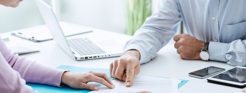 young woman meeting with accountant looking over papers for tax preparation services